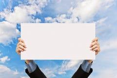 Hombre de negocios que lleva a cabo la muestra y la mano en blanco en cielo Imágenes de archivo libres de regalías