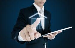 Hombre de negocios que lleva a cabo la tableta digital y el icono conmovedor de la casa en la pantalla, en fondo azul imagen de archivo
