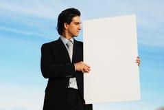 Hombre de negocios que lleva a cabo a la tarjeta en blanco fotos de archivo