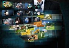 Hombre de negocios que lleva a cabo las imágenes que alcanzan que fluyen en manos Imagen de archivo