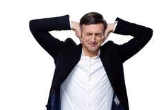 Hombre de negocios que lleva a cabo las manos en los oídos Imagen de archivo