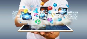 Hombre de negocios que lleva a cabo los dispositivos de la tecnología y los usos de los iconos sobre el A.C. Imágenes de archivo libres de regalías