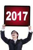 Hombre de negocios que lleva a cabo los números 2017 en un tablero Fotografía de archivo libre de regalías