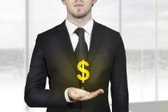 Hombre de negocios que lleva a cabo símbolo de oro del dólar Imagen de archivo libre de regalías