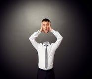 Hombre de negocios que lleva a cabo a su cabeza sorprendente en manos Fotografía de archivo libre de regalías