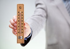 Hombre de negocios que lleva a cabo temperatura alta de lectura del termómetro Fotos de archivo libres de regalías