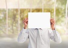 Hombre de negocios que lleva a cabo un cartel en blanco delante de su cara Fotografía de archivo libre de regalías