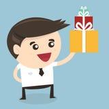 Hombre de negocios que lleva a cabo un regalo de Navidad grande de la caja de regalo Imagen de archivo libre de regalías