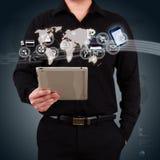 Hombre de negocios que lleva a cabo un uso del mapa y del icono de la demostración de la tableta encendido Fotos de archivo libres de regalías