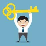 Hombre de negocios que lleva a cabo una llave de oro del éxito Imagen de archivo libre de regalías