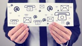 Hombre de negocios que lleva a cabo una muestra con los iconos del contacto Fotos de archivo libres de regalías