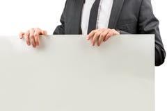 Hombre de negocios que lleva a cabo una muestra en blanco Foto de archivo libre de regalías