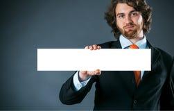 Hombre de negocios que lleva a cabo una muestra en blanco rectangular Foto de archivo