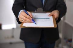 Hombre de negocios que lleva a cabo a una tarjeta blanca en blanco Foto de archivo libre de regalías