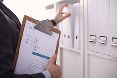 Hombre de negocios que lleva a cabo a una tarjeta blanca en blanco Imagenes de archivo