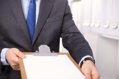 Hombre de negocios que lleva a cabo a una tarjeta blanca en blanco Imagen de archivo