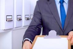 Hombre de negocios que lleva a cabo a una tarjeta blanca en blanco Fotografía de archivo