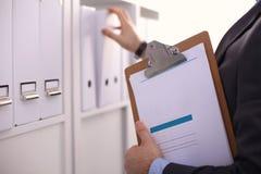 Hombre de negocios que lleva a cabo a una tarjeta blanca en blanco Fotografía de archivo libre de regalías