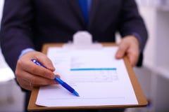 Hombre de negocios que lleva a cabo a una tarjeta blanca en blanco Imagen de archivo libre de regalías