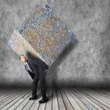 Hombre de negocios que lleva el paquete de piedra pesado Fotografía de archivo libre de regalías