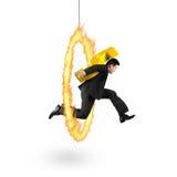 Hombre de negocios que lleva la muestra de dólar de oro que salta a través de aro del fuego Foto de archivo libre de regalías