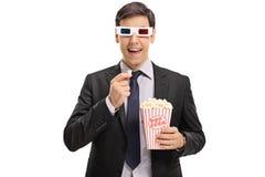 Hombre de negocios que lleva un par de los vidrios 3D y que come palomitas Foto de archivo libre de regalías