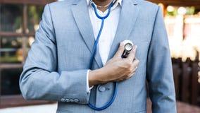 Hombre de negocios que lleva un traje con el estetoscopio imagen de archivo libre de regalías