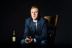 Hombre de negocios que lleva una chaqueta con el vidrio de whisky que se sienta en silla Alcohol de la botella en el fondo oscuro imagenes de archivo