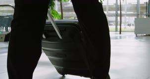 Hombre de negocios que lleva una maleta en la oficina 4k almacen de metraje de vídeo