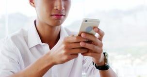 Hombre de negocios que manda un SMS y que espera a su almuerzo almacen de metraje de vídeo