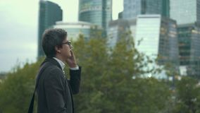 Hombre de negocios que marca un teléfono y que habla en una ciudad, una admiración y nuevas perspectivas