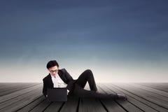 Hombre de negocios que mecanografía en el ordenador portátil al aire libre Imagen de archivo libre de regalías
