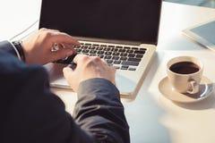 Hombre de negocios que mecanografía en el ordenador portátil con la pantalla en blanco en el lugar de trabajo Imagen de archivo libre de regalías