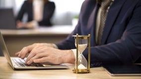 Hombre de negocios que mecanografía en el ordenador portátil en el escritorio, reloj de arena que gotea, acercamiento del plazo imagen de archivo libre de regalías