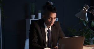 Hombre de negocios que mecanografía en el ordenador portátil tarde en oficina oscura