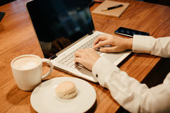 Hombre de negocios que mecanografía en el teclado del ordenador portátil tenga taza con el café, mac Fotografía de archivo