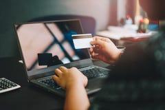 Hombre de negocios que mecanografía en el teclado del ordenador portátil y que sostiene la tarjeta de crédito encendido fotos de archivo libres de regalías