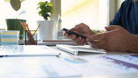 Hombre de negocios que mecanografía en el teclado, trabajos con smartphone y un ordenador portátil almacen de metraje de vídeo