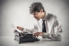 Hombre de negocios que mecanografía en la máquina de escribir foto de archivo