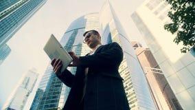 Hombre de negocios que mecanografía en una tableta cerca del centro de negocios, visión inferior
