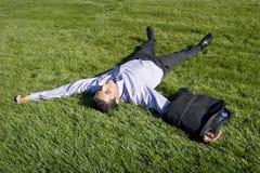 Hombre de negocios que miente en hierba imagen de archivo