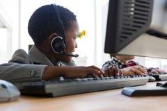 Hombre de negocios que mira ausente mientras que habla a través de las auriculares el escritorio fotografía de archivo libre de regalías