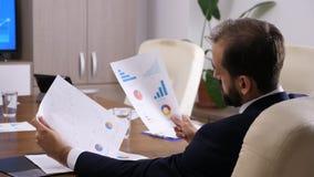 Hombre de negocios que mira cartas y gráficos almacen de video