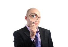 Hombre de negocios que mira con magnificar Imágenes de archivo libres de regalías