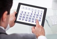 Hombre de negocios que mira el calendario en la tableta digital Imágenes de archivo libres de regalías