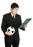 Hombre de negocios que mira el cojín del fichero y que sostiene el balón de fútbol Imagen de archivo libre de regalías
