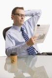Hombre de negocios que mira el papeleo - aislado Fotografía de archivo libre de regalías