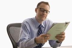 Hombre de negocios que mira el papeleo - aislado Fotos de archivo