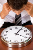 Hombre de negocios que mira el reloj en oficina con la cabeza en manos Foto de archivo