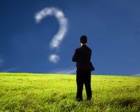 Hombre de negocios que mira el signo de interrogación Imágenes de archivo libres de regalías
